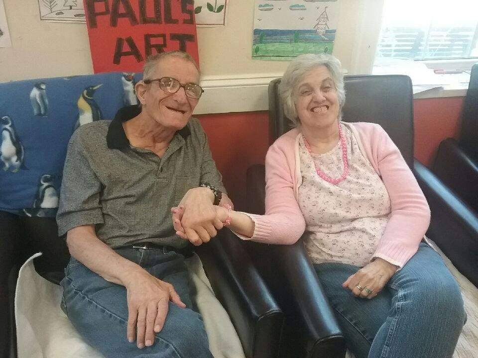 Two seniors with disabilities holding hands