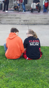 Two individuals sitting on the grass in front of a band playing