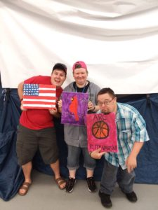Three people with disabilities showing off their paintings