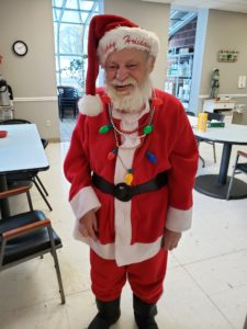 A senior man with disabilities smiling in his Santa costume
