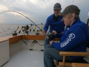 Respite staff assisting an older man with disabilities in fishing for king salmon on a fishing charter