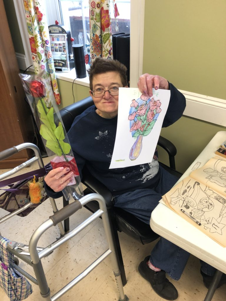 An adult woman with disabilities holds up a completed coloring page showing a bouquet of flowers