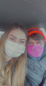 A staff member and person supported by the Arc sitting next to each other in a vehicle with masks on.